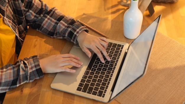Обрезанный снимок женских рук, печатающих на клавиатуре ноутбука на деревянном столе в комнате домашнего офиса