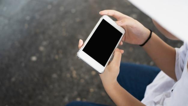 Обрезанный снимок женщины, держащей горизонтальный смартфон.