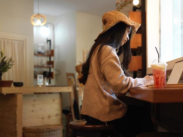 セーターと帽子のカフェのカウンターバーに座っている間ノートパソコンでの作業で女性のトリミングされたショット