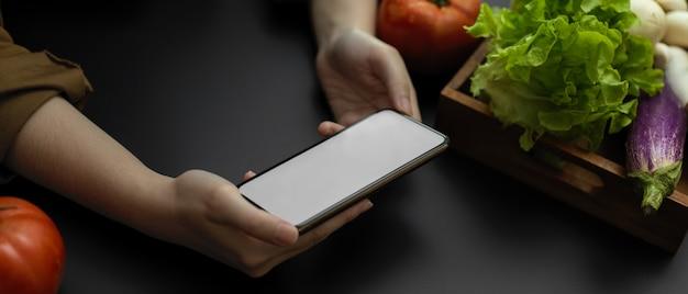 新鮮な野菜の食材を準備しながら、水平の空白の画面のスマートフォンでレシピを探している女性のショットをトリミング