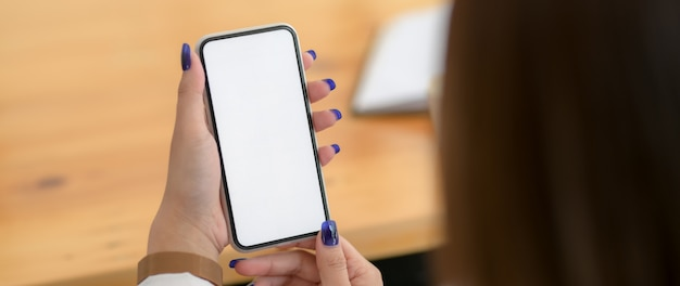 木製の机の上のスマートフォンを使用して女性のショットをトリミング