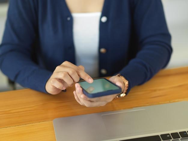 Обрезанный снимок женщины, использующей смартфон во время работы с ноутбуком на деревянном столе