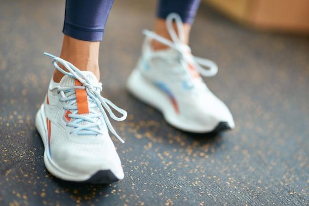 ジムに立っているスポーツシューズやスニーカーを履いている女性のクロップドショット。トレーニング、トレーニング、健康的でアクティブなライフスタイルの概念
