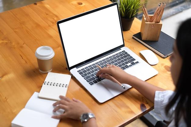 カフェのクリッピングパスで木製のテーブルにノートパソコンと文房具を使用して作業している女性のクロップドショット