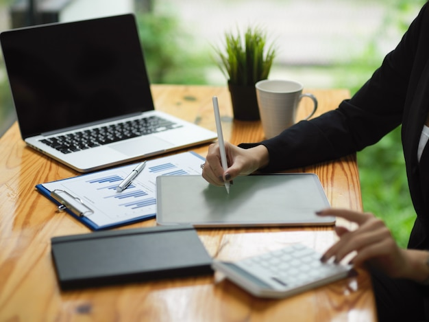 カフェでラップトップを搭載したスマートデジタルタブレットでスタイラスペンを使用して正式な女性労働者のトリミングされたショット