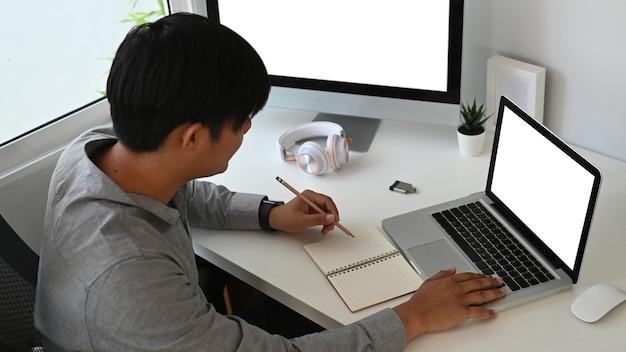 Обрезанный снимок графического дизайнера или фотографа сидит за столом и делает заметки в записной книжке.