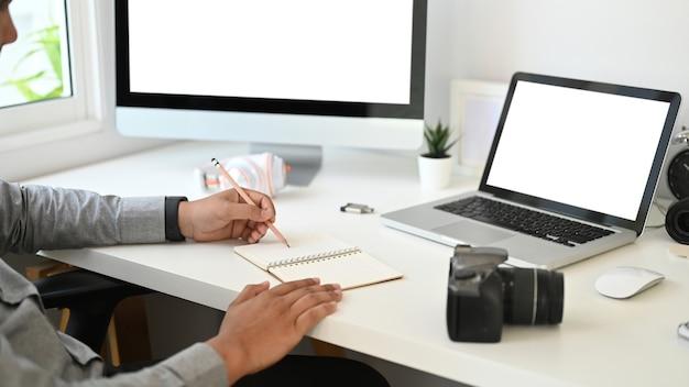 Обрезанный снимок графического дизайнера или фотографа пишет на пустой записной книжке на столе.