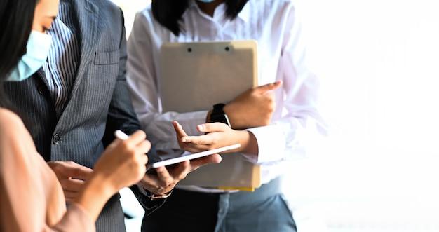 디지털 태블릿을 사용하고 함께 새로운 아이디어를 논의하는 직원 그룹의 자른 사진.