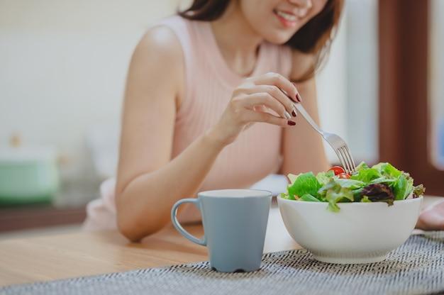 キッチンの白いボウルで新鮮な野菜サラダを食べる幸せな女性のクロップドショット。健康的な食事を楽しむ