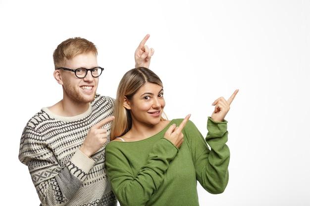 幸せな若い夫婦の男性と女性が互いに近くに立って、元気に笑って、あなたの広告のために白いコピースペースの壁に指を向けるのトリミングされたショット