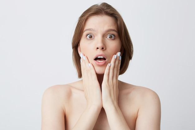 Обрезанный снимок впечатленной удивленной молодой женщины с темными волосами