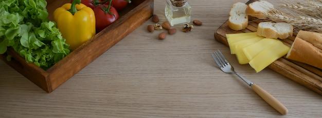 나무 주방 용품에 프랑스 버 게 트 빵, 치즈, 야채와 함께 식탁의 자른 샷