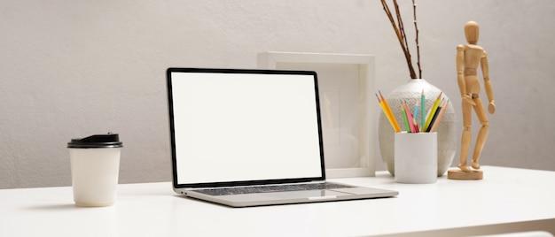 Обрезанный снимок ноутбука с обтравочным контуром на белом столе с канцелярскими принадлежностями и украшениями в домашнем офисе