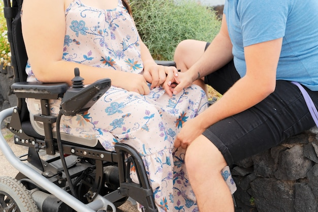 愛するカップル、障害者のガールフレンドとデート中に手をつないで車椅子の妻と若い男のトリミングされたショット