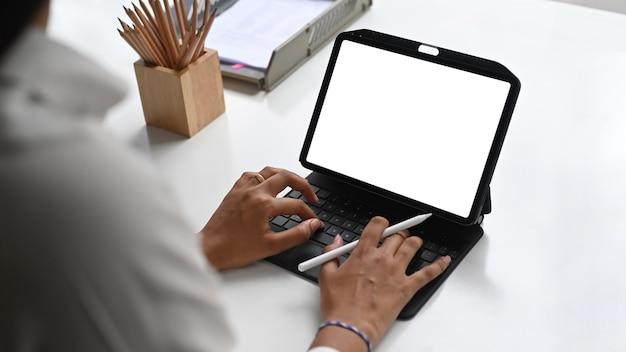 白いオフィスの机の上の空白の画面でデジタルタブレットで作業している男性のフリーランサーのトリミングされたショット。
