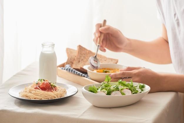 自宅のキッチンのテーブルでサラダ、カボチャのピューレ、スパゲッティ、ミルクと一緒に朝食をとっている男性のクロップドショット