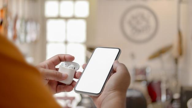 Обрезанный снимок мужчины, держащего беспроводные наушники и смартфон с пустым экраном