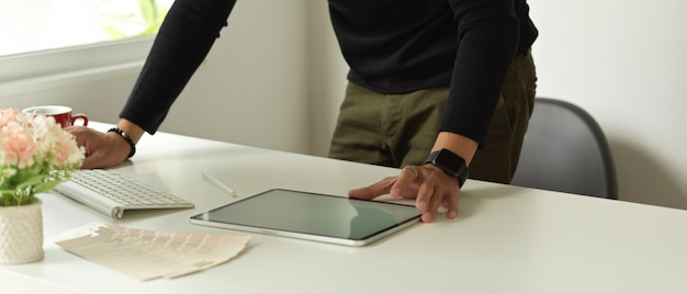 白いテーブルの上でタブレットや事務用品を扱う男性のクロップドショット