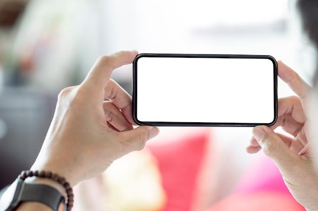 水平方向のビューで空白の画面のスマートフォンを持っている男の手のトリミングされたショット。