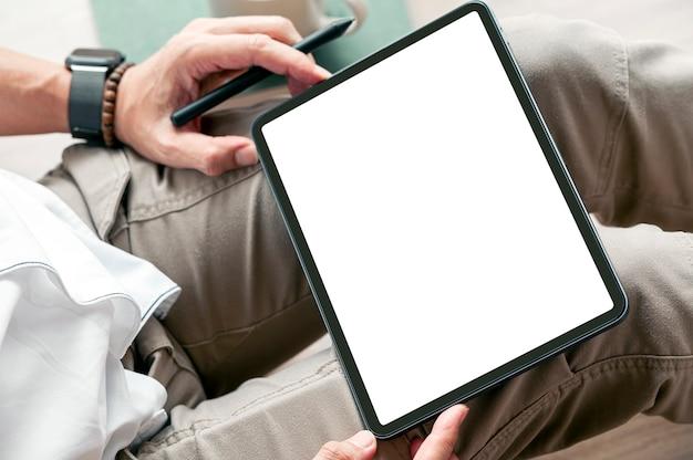 집에서 바닥에 앉아있는 동안 빈 화면 태블릿을 들고 남자 손의 자른된 샷.