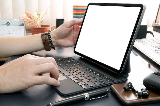 Обрезанный снимок руки человека, работающего на планшетном компьютере, сидя за офисным столом