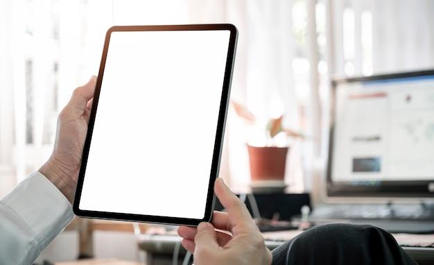 Обрезанный снимок мужской руки, держащей пустой экран планшета, сидя за офисным столом