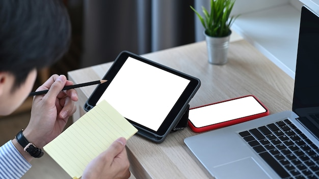 タブレットで作業し、机の上の個人的な紙にメモをとっている男性のクロップドショット。