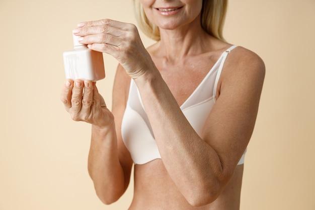 スキンケアクリームの白い瓶を保持し、開いている下着の成熟した女性のクロップドショットまたは