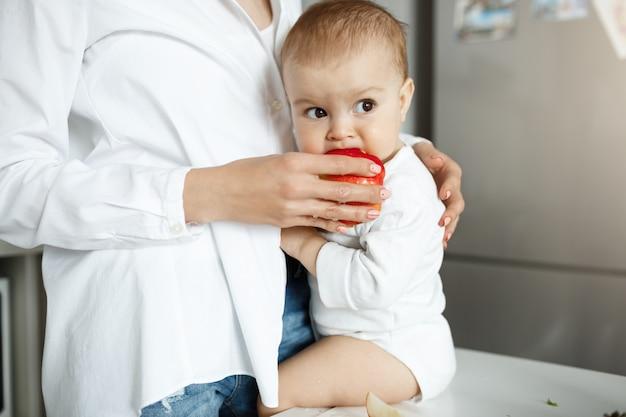 リンゴの赤ちゃんのスライスを与える母親のショットをトリミング