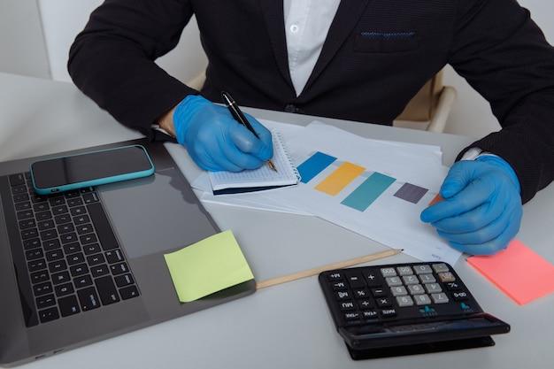 사무실에서 작업하는 동안 보고서를 계산하는 보호 장갑에 작업자의 자른 샷.