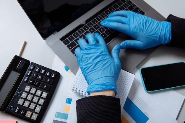 사무실에서 노트북으로 작업하는 동안 보호 장갑에 작업자의 자른 샷.