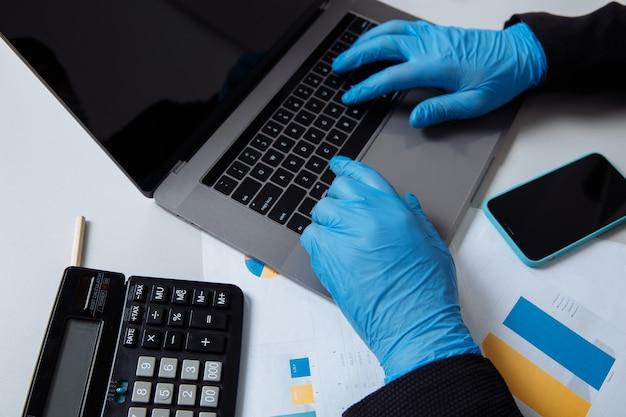 사무실에서 노트북으로 작업하는 동안 보호 장갑에 작업자의 자른 샷