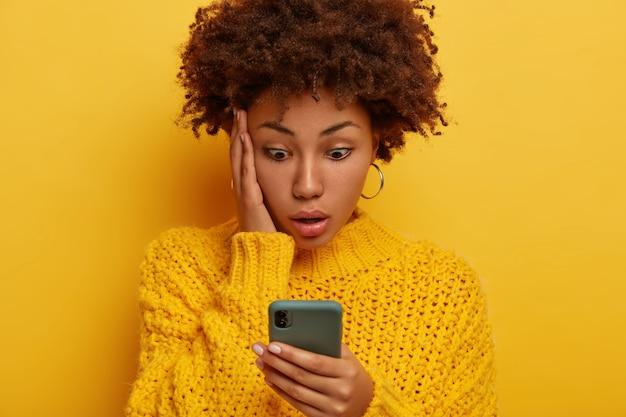 Обрезанный снимок ошеломленной кудрявой женщины, которая смотрит на дисплей смартфона, потрясенная, все песни исчезли из плейлиста, одетая в вязаный желтый свитер, держит ладонь на щеке, озадаченная и обеспокоенная.