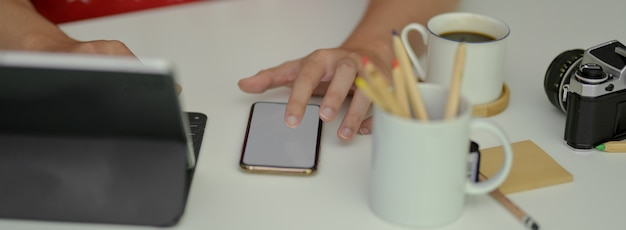 作業台で作業中にモックアップのスマートフォンに触れている写真家の写真をトリミング