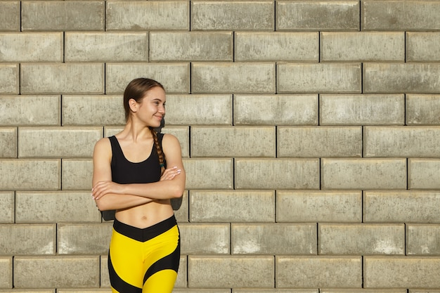 콘텐츠 복사 공간이 빈 벽돌 벽에 포즈, 야외 휴식을 갖는 유행 검정색과 노란색 스포츠 옷을 입고 긍정적 인 화려한 젊은 여자의 자른 샷