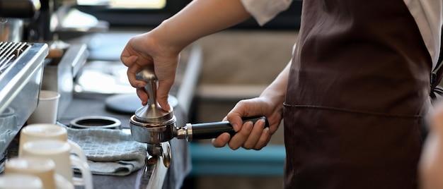 Обрезанный снимок профессионального бариста, измельчающего кофе в кафе