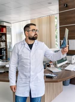 診療所に立ってx線診断を検査する放射線科医のトリミングされたショット。