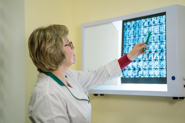 啓発されたボードの近くに立っている間にx線診断を調べる放射線科医のトリミングされたショット。