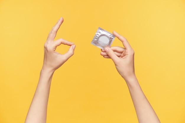 콘돔 팩과 함께 주황색 배경 위에 포즈를 취하는 동안 제기 된 여성의 손을 자른 샷, 상황이 통제되었음을 나타내면서 확인 제스처를 보여줍니다.