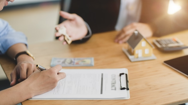 彼の顧客に家の鍵を与える不動産業者のショットをトリミング