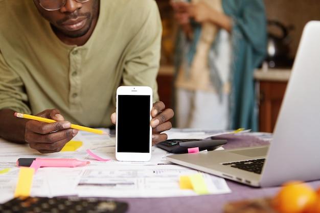 空白の画面の携帯電話で鉛筆を指しているメガネで深刻なアフリカ系アメリカ人のショットをトリミング
