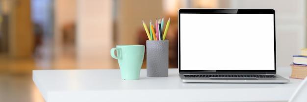 空白の画面のラップトップ、マグカップ、文房具、本、コピースペースを持つ単純なワークスペースのショットをトリミング
