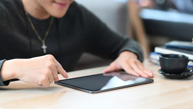 リビングルームに座ってデジタルタブレットを使用して笑顔の若い男のクロップドショット。