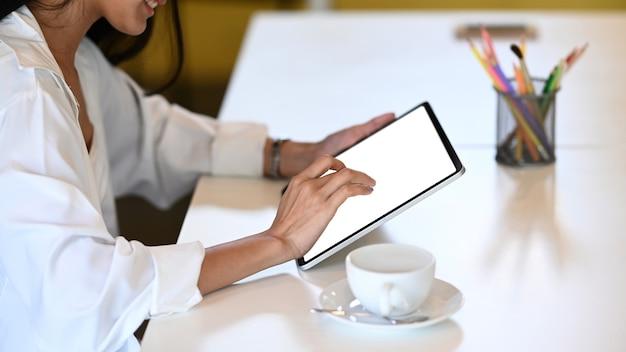 Обрезанный снимок улыбается дизайнер молодой женщины с помощью цифрового планшета в офисе.