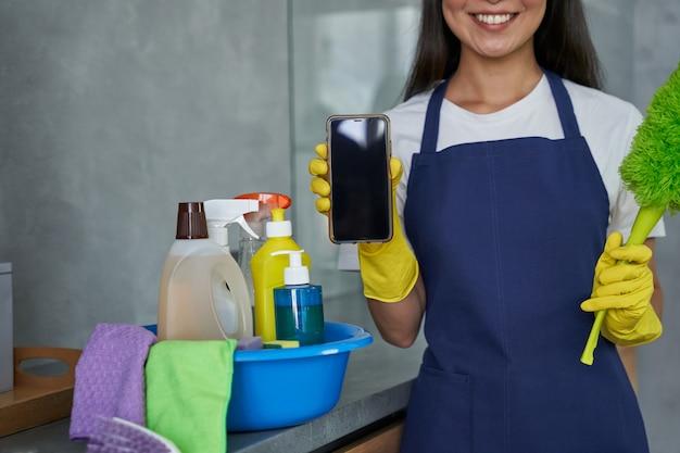 청소용 빗자루와 빈 화면이 있는 스마트폰을 들고 집을 청소할 준비가 된 보호 장갑을 끼고 웃고 있는 젊은 여성의 자른 사진. 가사 및 가사, 청소 서비스 개념