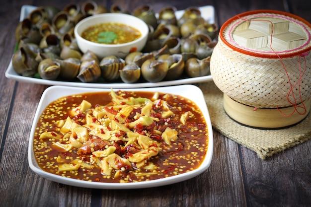 ソムタムまたはパパイヤのサラダのクロップドショット、もち米、リンゴのカタツムリの煮物、木製のテーブルにタイのスパイシーなチリソースを添えたタイの伝統料理。