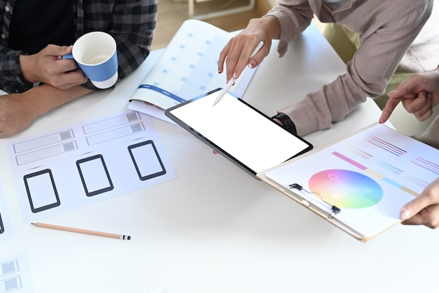 デジタルタブレットを使用し、クリエイティブオフィスでのカラーデザインについてブレーンストーミングを行うスタートアップチームのクロップドショット。