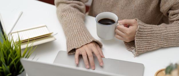 学生がコーヒーを持ちながらノートパソコンを使用してのショットをトリミング