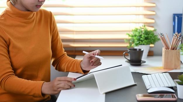 현대 사무실에서 디지털 태블릿으로 작업하는 세련된 여성의 사진을 잘랐습니다.