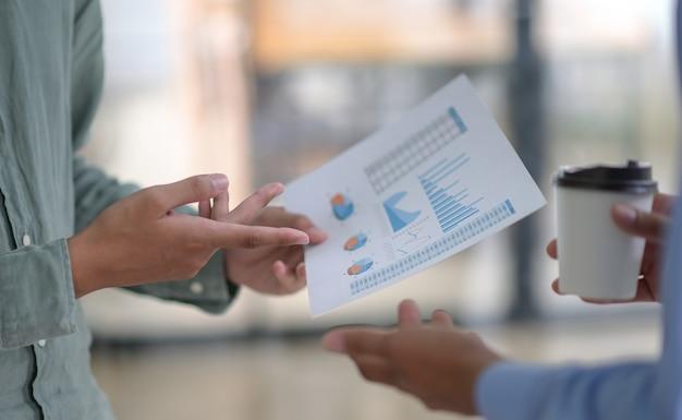 Обрезанный снимок команды-фрилансера, держа в руке графики и кофе.